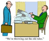 Old Rules. Business cartoon of businessman with stacks of binders on his desk who is saying, 'we're throwing out the old rules stock illustration