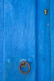 Old run-down blue painted wooden door and lock Royalty Free Stock Photography