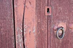 Old run-down red painted wooden door and lock Stock Photos