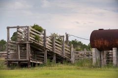 Old run down wooden cattle chute with rusty fuel tank nearby stock images