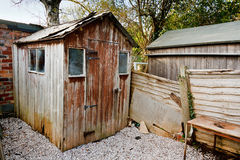 Old run down worn out rotting garden shed. Badly maintained old aged run down burlap panel wooden garden shed with damaged roof and hole from wood rot Royalty Free Stock Images