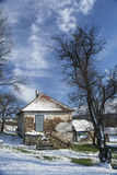 Old rural house covered with snow at a village Stock Images