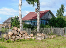Old rural house with pile of big wooden chocks in front Royalty Free Stock Photography