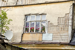 Old rural house window with flowers and satelite dish Royalty Free Stock Image