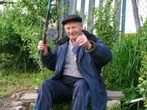 Old rural man brags a caught small fish. Sitting on the bench old rural man brags a caught small fish stock photos
