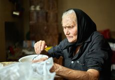 Elderly woman eating soup. Old rural woman eating her soup from a bowl Royalty Free Stock Image