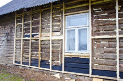Old rural wooden house restoration and insulation Royalty Free Stock Images