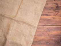 Old rural wooden table boards and burlap vintage background, photo top view. Hessian, sacking texture on wooden Royalty Free Stock Image