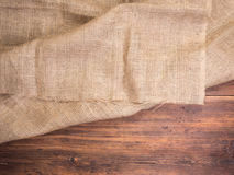 Old rural wooden table boards and burlap vintage background, photo top view. Hessian, sacking texture on wooden Royalty Free Stock Photos