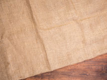 Old rural wooden table boards and burlap vintage background, photo top view. Hessian, sacking texture on wooden Stock Images