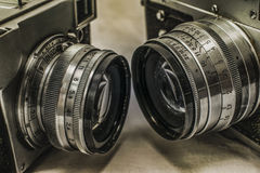 Old Russian analog film cameras with manual controls. Close up view of two old Russian analog film cameras with the lenses facing each other on dirty canvas with stock images