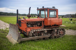 Old russian bulldozer. Old, orange russian bulldozer in a farm royalty free stock image