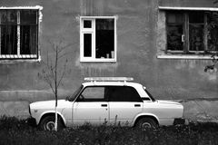 Old Russian Car - white Lada. Parked next to an apartment building in Russia. Black and white image Stock Image