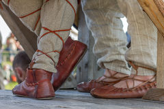 Old russian leather sandals on men's feet. On the wooden floor Royalty Free Stock Images