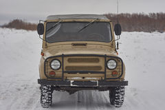 Old russian off-road vehicle, 4x4 car. snowy road,cloudy sky Royalty Free Stock Images