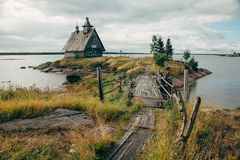 Old russian Orthodox wooden church in the village Rabocheostrovsk, Karelia. Abandoned church on the coastline. Old russian Orthodox wooden church in the village royalty free stock images