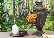 Old Russian samovar with bagels on a wooden table royalty free stock image