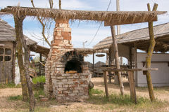 Old Russian stove under thatched shed in yard outdoors Royalty Free Stock Images