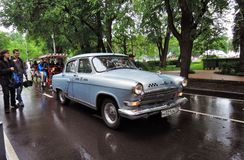Old Russian taxi car drives on the wet road Stock Photo