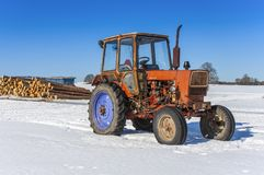 Old Russian tractor in snow. Y field stock images