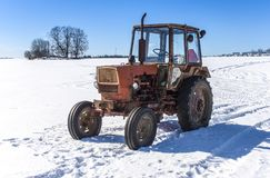 Old Russian tractor in snow. Y field royalty free stock image