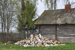 Old russian village house with a bundle of firewood. Old house in a Russian village with the prepared firewood for winter royalty free stock image