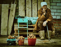 Old Russian woman selling potatoes Kaluga region. Older women in Russia often continue to work, growing and selling farming products such as potatoes royalty free stock images