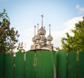 Old Russian wooden church. View over fence. Old Russian wooden church among trees and on blue sky background. View over green plank fence. Historical and holy Stock Image
