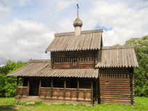 Old Russian wooden log tower with cupolas. And crosses among green grass in the summer Stock Images