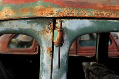 Using a spike as a hinge pin in an old rusty car. royalty free stock photos