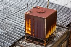 Rust water storage tank on the roof of the house. Old rust water storage tank on the roof of the house Stock Image