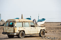Old rusted 4x4 on a beach in Oman Stock Image
