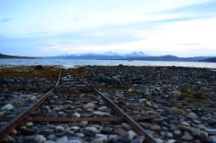 Old rusted boat landing ramp on sea shore with fjord and snowy mountain Royalty Free Stock Photos