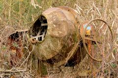 Old rusted cement mixer stands overgrown in a leafless hedge. Old rusted cement mixer stands overgrown in a leafless thorn hedge royalty free stock photos
