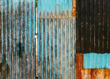 Old rusted corrugated gate. Old rusted corrugated blue gate, grungy texture or background. Gate shut with a lock royalty free stock photos