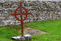 Old, rusted cross marking a grave, with stone wall behind Royalty Free Stock Image