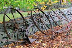 Old rusted farming equipment leaning against stonewall Stock Photo