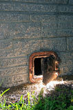 Old rusted iron door ajar at night. A partially open old rusted iron door sits close to the ground on the outside wall of a stone brick chimney, lit from the Royalty Free Stock Photo