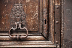 Old rusted knocker on brown wooden door Royalty Free Stock Photos