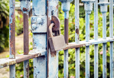 Old rusted lock on blue rusty iron gate Stock Images