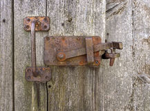 Old rusted locking. With vertical grasp on the weathered gray wooden wall of a shed Royalty Free Stock Photo