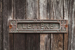 Old rusted mailbox in dark brown wooden door Royalty Free Stock Photography