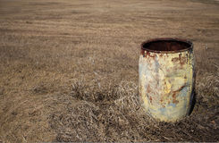 Old rusted metal barrel on brown grass Royalty Free Stock Photos