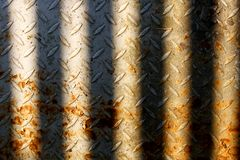 Old rusted metal plate sun-lit between bars. Old and rusted metal plate sun-lit between some bars, probably good for texture stock photo