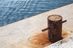 Old rusted mooring bollard on concrete pier Royalty Free Stock Photo
