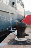 Old rusted mooring bollard with knotted nautical ropes Stock Images