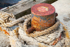Old rusted mooring bollard with naval ropes Stock Photos