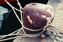 Old rusted mooring bollard with naval ropes Royalty Free Stock Photo