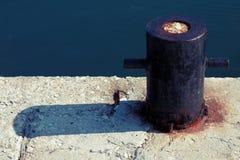 Old rusted mooring bollard on the sea coast Stock Photo