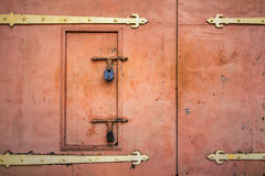 Old rusted padlock hanging on gray metal retro door Royalty Free Stock Photo